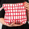 holding red square wash bag